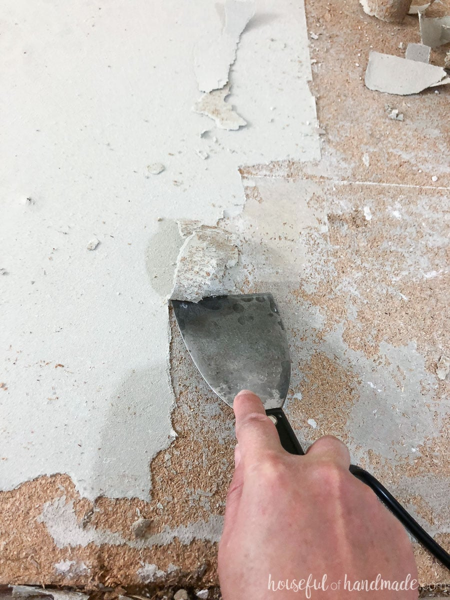 Scrape the layers of old linoleum off the floor with a heat gun and putty knife.
