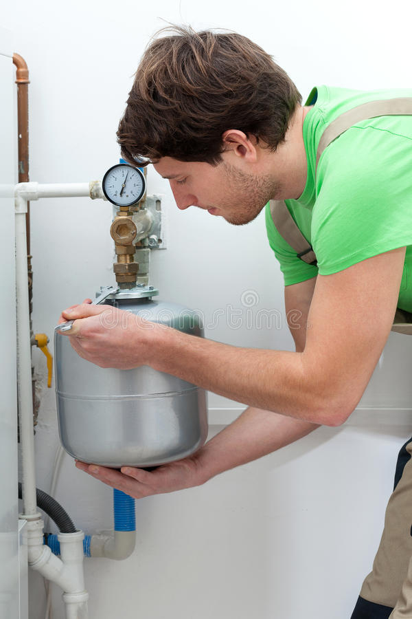 Boiler installation. Young worker installing small silver boiler in house royalty free stock photography