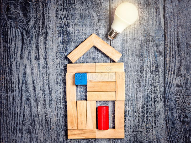 Form of house above tree on dark wooden background and LED bulb. Imitation of heating copper or boiler and air conditioner. Home improvement concept. Idea for royalty free stock image