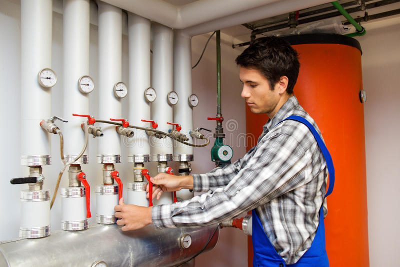 Heating engineer in a boiler room for heating. Young heating engineer in a boiler room for heating system royalty free stock photo