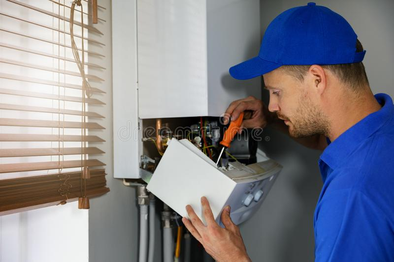 House gas heating boiler maintenance and repair service. Worker in blue uniform stock photography