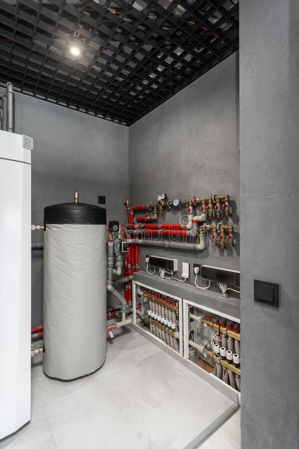 Technical boiler room in new modern house. Vertical photo of technical boiler room in new modern house with filter on water tank capacity, pipes equipment stock photo