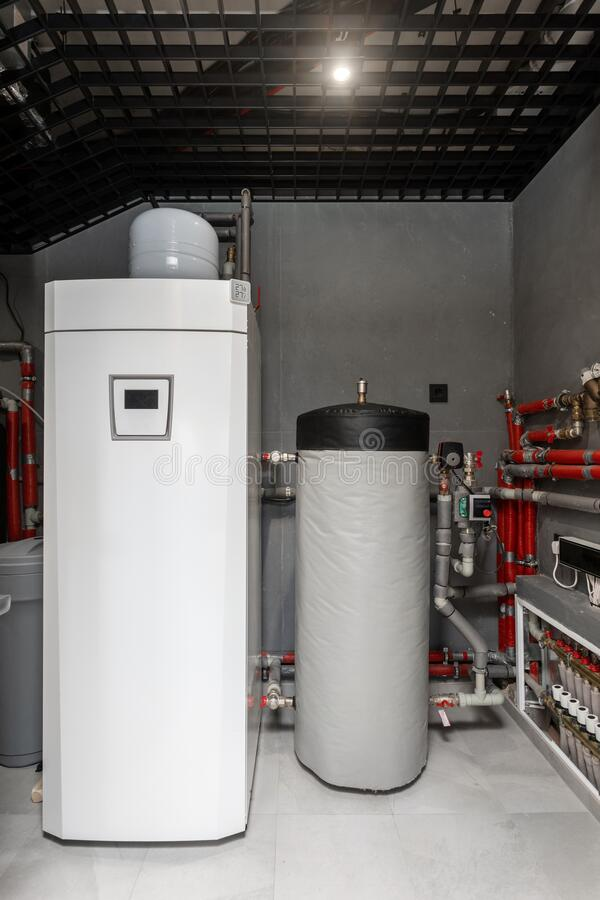 Technical boiler room in new modern house. Vertical photo of technical boiler room in new modern house with large water tank capacity, pipes, plumbing stuff and royalty free stock photography