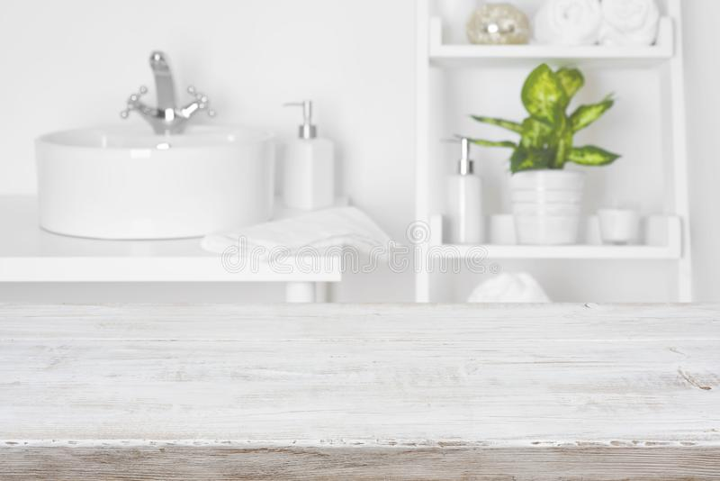 Wooden table in front of blurred white bathroom shelves background stock images