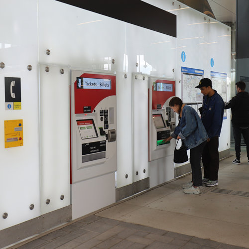 Customers using a ticket machine at Bayview Station.